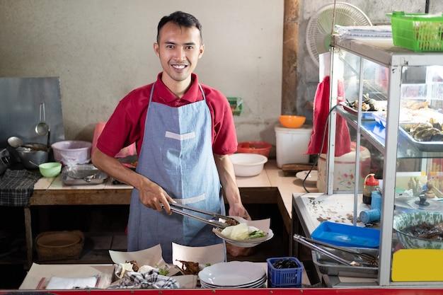 アジアの屋台のウェイターは、屋台で顧客の注文のためのおかずを準備している間、トングを持って立っています