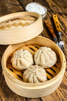 Asian steamed dumplings manti in a bamboo steamer.