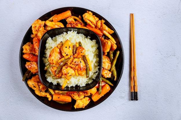 Азиатское жаркое из мяса, овощей с белым рисом и палочками для еды.