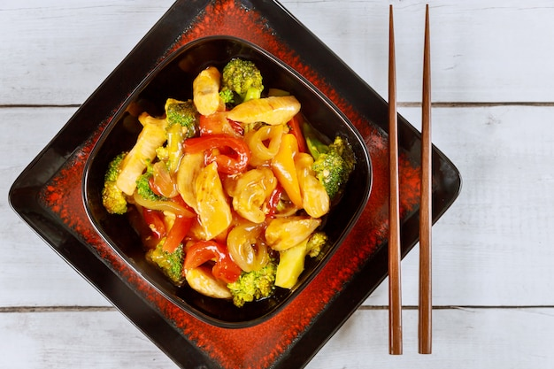 Asian stir fry meat with paprika, onion and broccoli in square bowl.