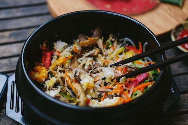 Alimento asiatico della via in piatto di plastica nero con le bacchette