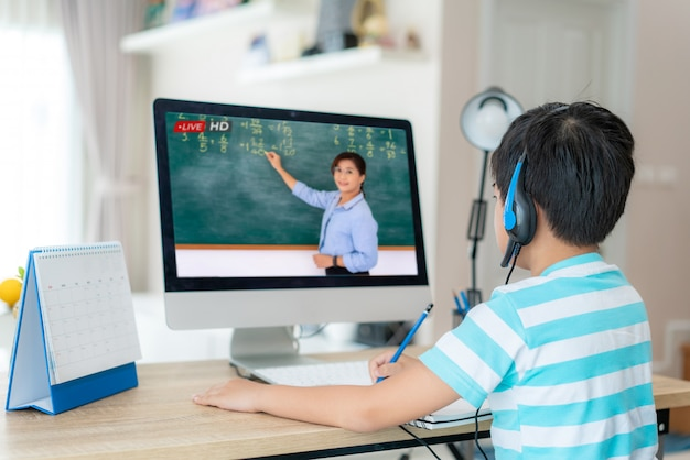 Asian student boy video conference e-learning with teacher on computer in living room at home