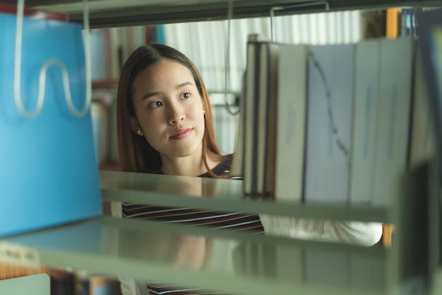 Asian student choosing book in the shelf in library.