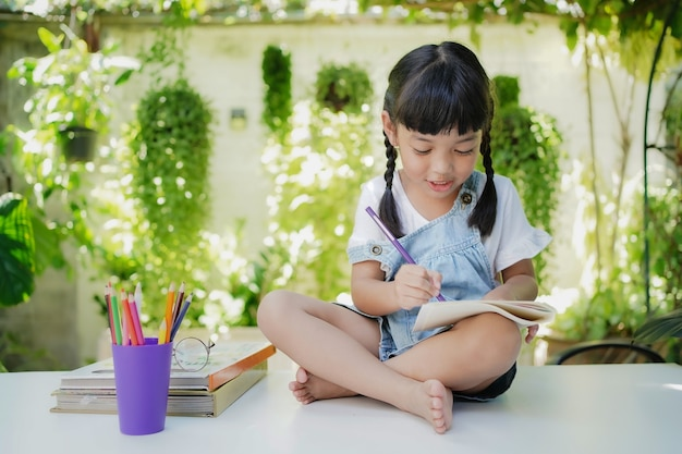 Asian student cute girl drawing and writing on the book for homework at home.