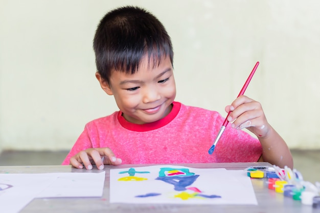 Asian student drawing and painting colours on the paper in the room.