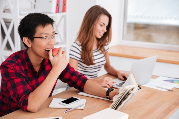 Asian student eating apple and reading while groupmate working at laptop