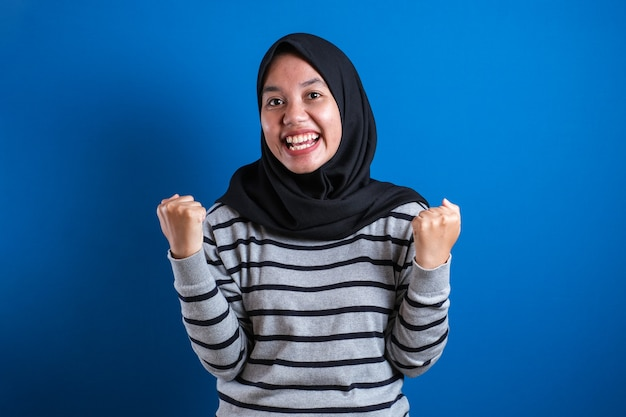 Asian student girl in headscarf celebrating success with raised hands and clenched fists
