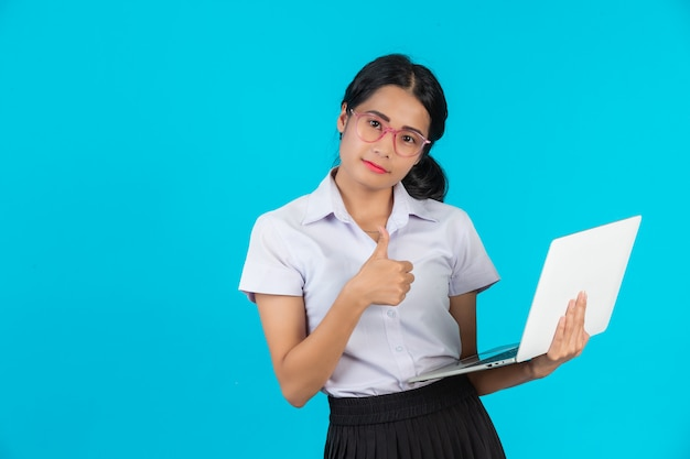 An asian student girl holding her notebook on a blue .