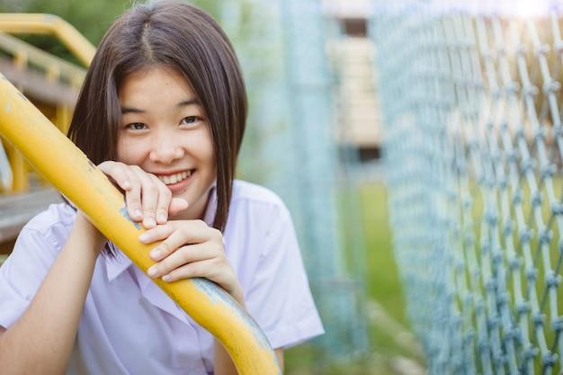 アジアの学生の女の子の十代の無邪気な恥ずかしがり屋の笑顔とコピースペース付きのカメラを探しています