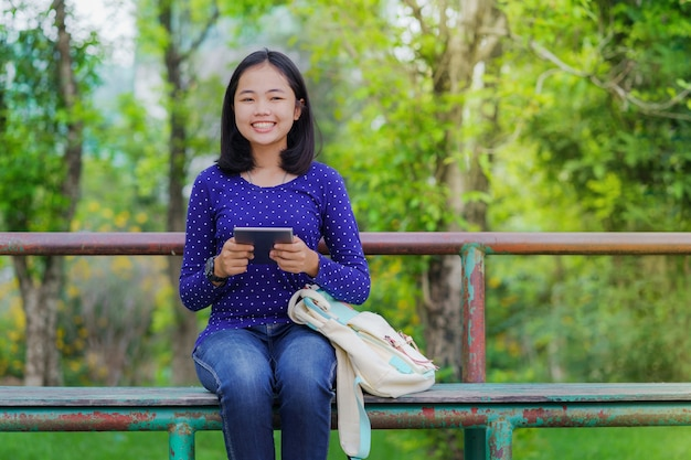 Asian student girl using a digital tablet in the park in a sunny summer day