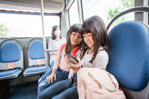 学校に行く途中で一緒に公共バスに乗ってスマートフォンを使用してアジアの学生の女の子