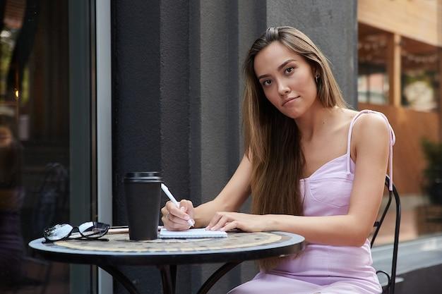 Азиатская студентка с чашкой кофе за пределами кафе изучает написание заметок
