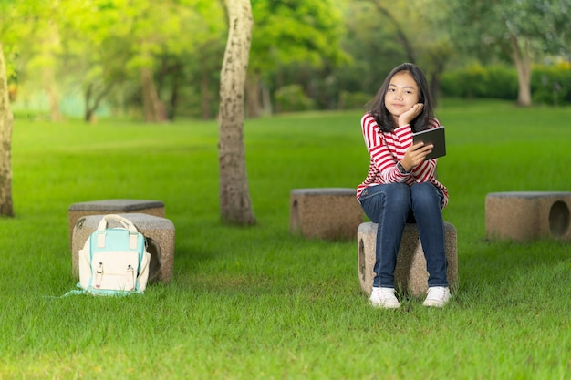 Asian student girl with a digital tablet in the school park in a sunny summer day