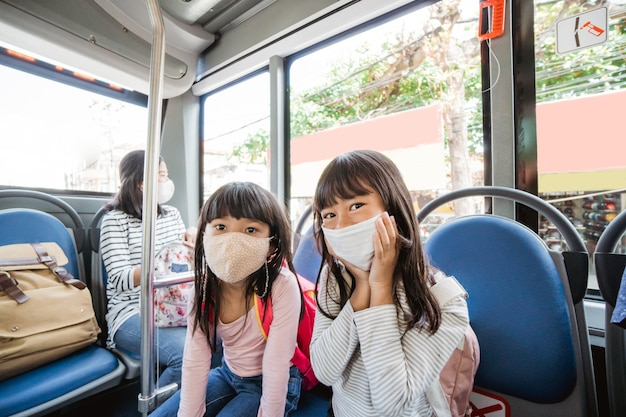公共交通機関で一緒に学校に通うアジアの学生