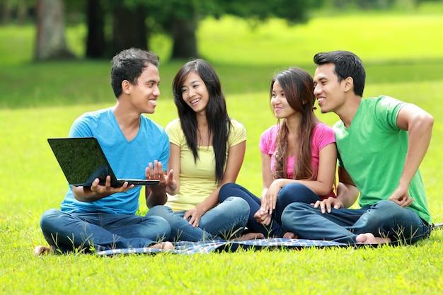 公園で勉強しているアジアの学生グループ