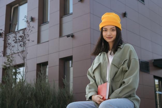 大学のキャンパスに座っているカメラを見ている本を持っているアジアの学生