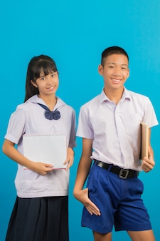 An asian student holding a notebook andasian male student holding a green board on a blue .