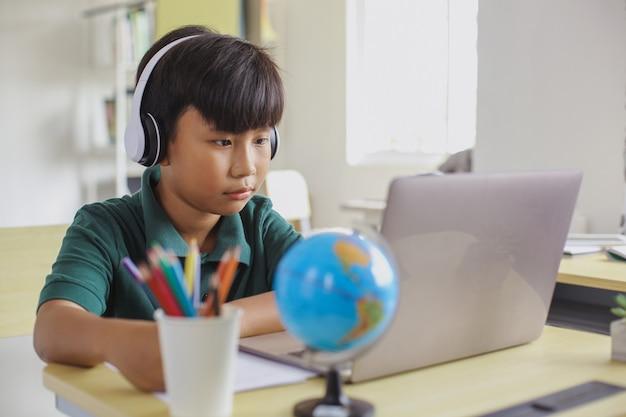 ノートパソコンを見ながら紙にヘッドフォンで書くアジアの学生