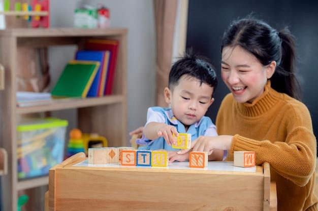 유치원에서 아시아 학생은 편지 상자를 사용하여 선생님과 함께 교실에서 공부 단어를 만듭니다.