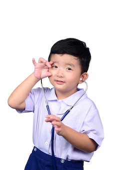 Asian student kid in school uniform playing medical stethoscope with clipping path.