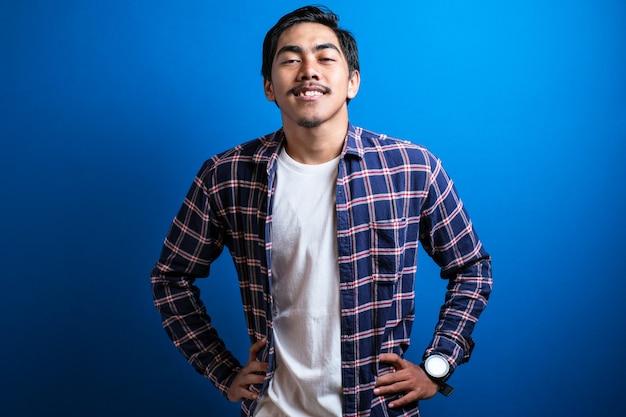 아시아 학생 남자는 파란색 배경에 대해 두 손을 허리에 대고 자신감을 보이는 카메라를 향해 미소를 지었습니다. 스튜디오 촬영