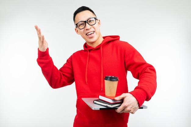 한 잔의 커피와 흰색 배경에 노트북과 책을 가진 아시아 학생 남자
