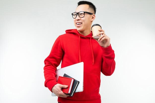 한 잔의 커피와 흰색 배경에 노트북과 책 아시아 학생 남자.