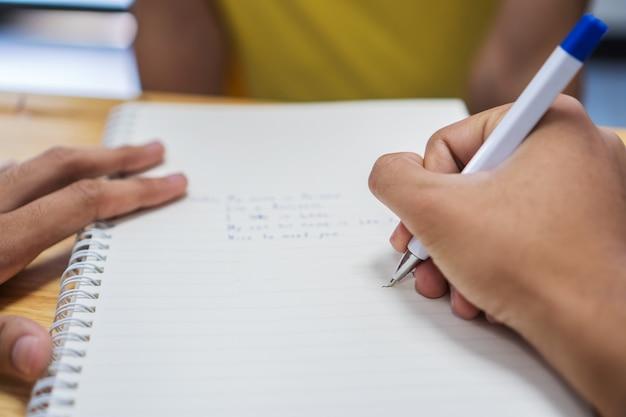 Записка азиатского студента на тетради во время изучения учебы и письма для планирования работы. обучение в сфере образования