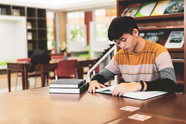 Asian student reads book in the library, lessons for exams, educational concepts
