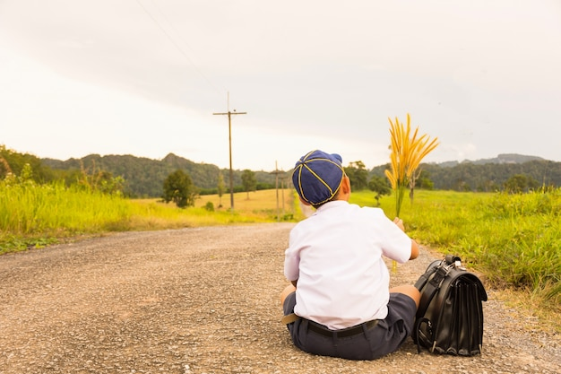 Asian student sitting  and country view