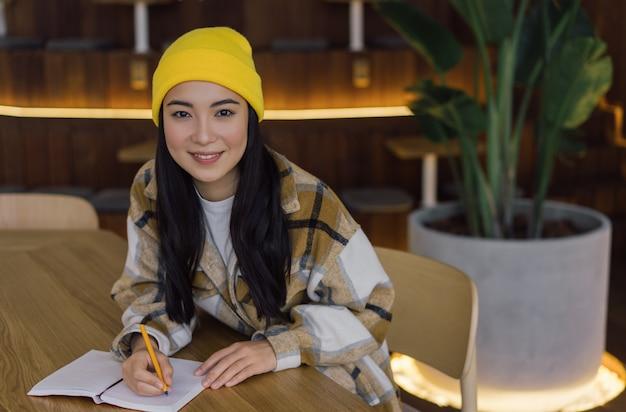アジアの学生の勉強、試験準備、メモを取る。在宅勤務の韓国人フリーランサーの肖像画