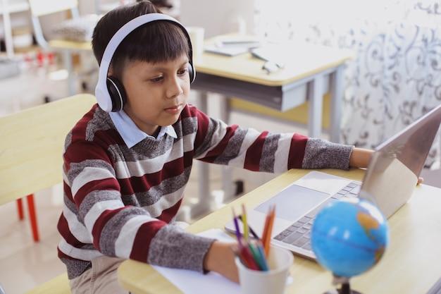 ノートパソコンを使用して勉強しているアジアの学生