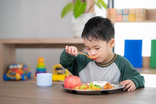 아시아 학생이 유치원에서 준비한 음식 트레이로 교실에서 점심을 먹습니다.