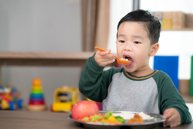 Asian student take a lunch in class room by food tray prepared by his preschool