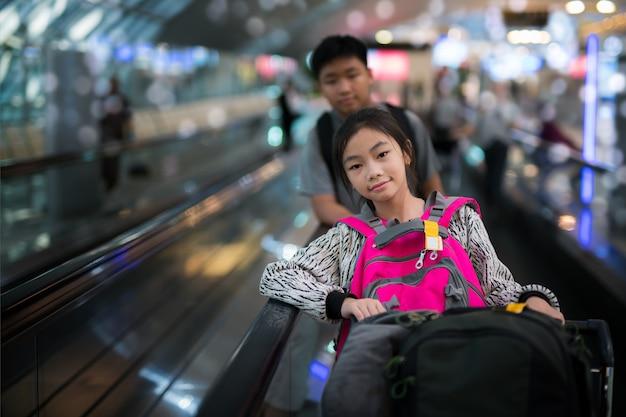 アジアの学生が国際空港のフライト間を乗り継ぐ