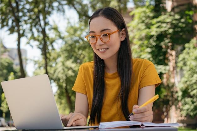 ラップトップコンピューターを使用して試験準備を勉強しているアジアの学生