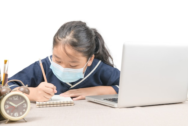 Asian student wearing protective mask,taking notes from laptop computer,writing do homework, new normal and prevent covid 19 infection