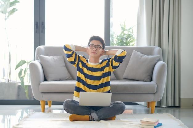 집에서 시험을 준비하는 많은 책과 노트북을 가진 아시아 학생