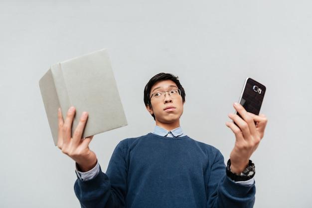 책과 phone.from 아래에서 아시아 학생. 놀란