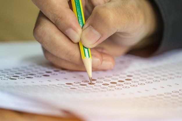 연필을 손에 들고 객관식 퀴즈 또는 시험 시험 답안지 연습을하는 아시아 학생들