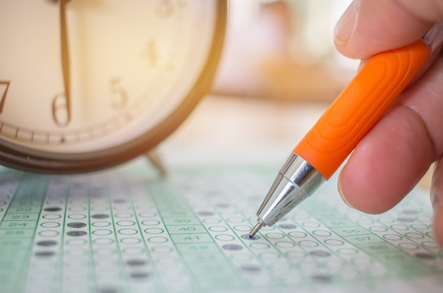 Asian students taking optical form of standardized exams near alarm clock