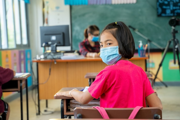 Asian students wearing protective mask in elementary room.