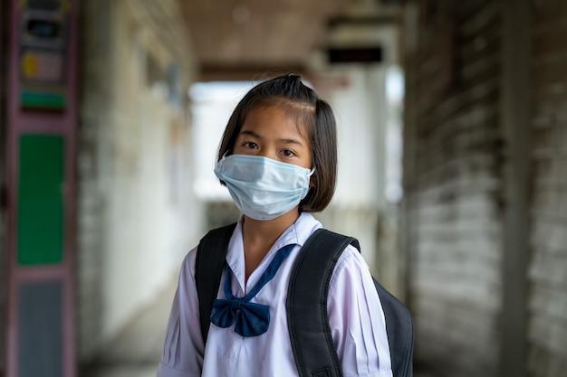 Covid-19から保護するために保護マスクを身に着けているアジアの学生は、学校に戻って彼らの学校、教育、小学校を再開します。