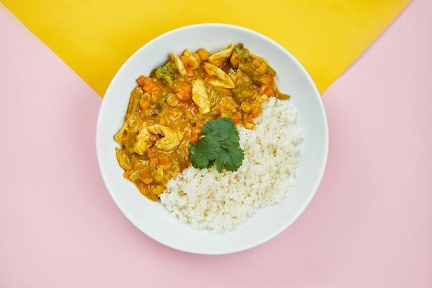 アジアンスタイルの料理-色とりどりの表面に白いボウルにライス添え野菜とチキンカレー。ミニマルな食べ物。上面図