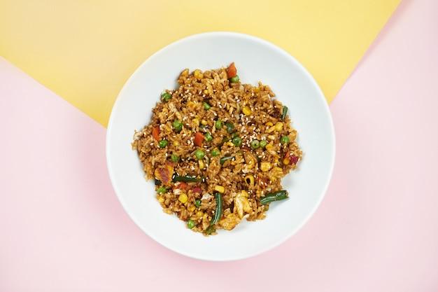 アジアンスタイルの料理-色とりどりの表面に白いボウルに野菜と鶏肉を入れた中華炒飯。ミニマルな食べ物。上面図
