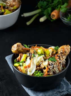 Asian-style lunch with noodles with chicken in teriyaki sauce, vegetables, spices and microgreens