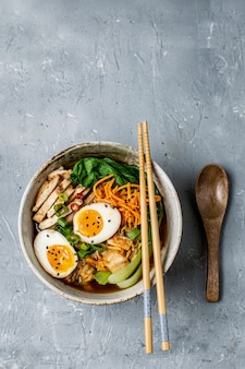 Asian style ramen noodle soup with bok choy, carrot, lime, sesame seeds, chicken and egg
