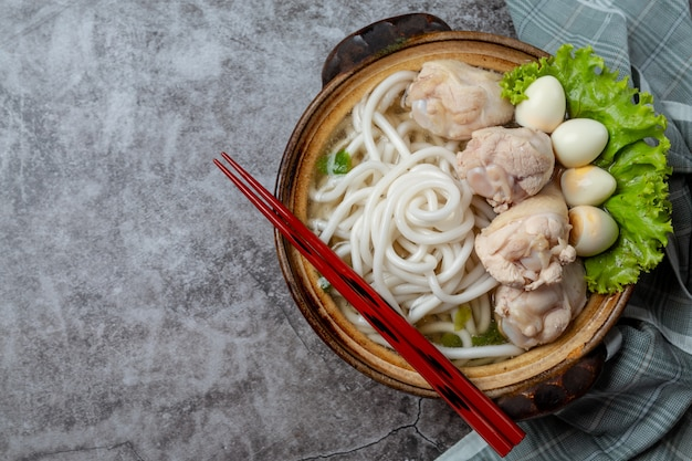 Asian style soup with noodles, pork and green onions closely in a bowl on the table.