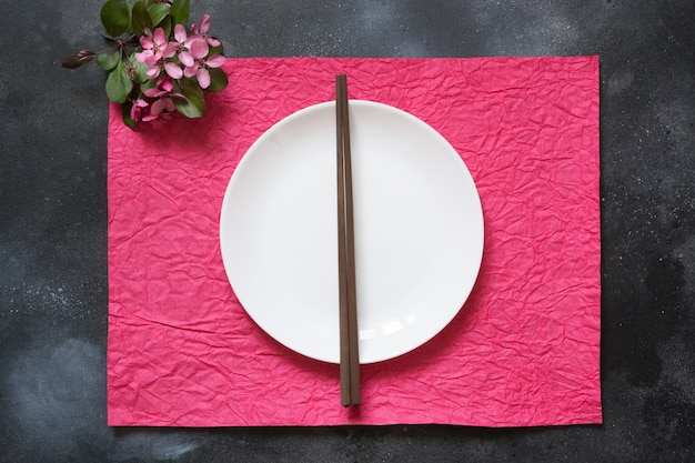 Asian style tableware. white plate with bamboo chopsticks on red napkin. top view.
