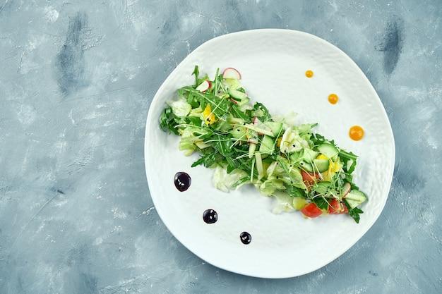 白いプレートにルッコラ、トマト、オレンジ、レタスのアジアンスタイルのベジタリアンサラダを残します。上面図